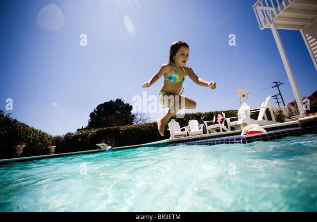 young kids swimming in backyard pool - Stock Image
