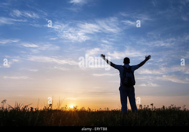 Silhouette of man with arms raised up and beautiful sky. Element of design. Summer sunset. Background - Stock Image