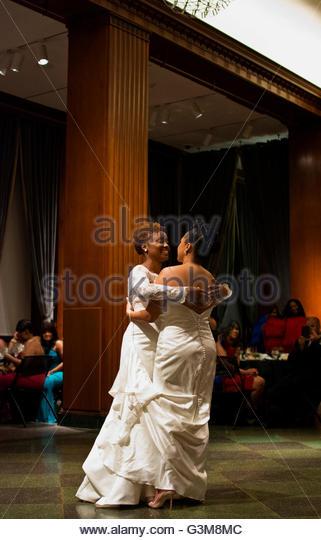 Bride couple wearing wedding dresses having first dance in wedding reception ballroom - Stock Image