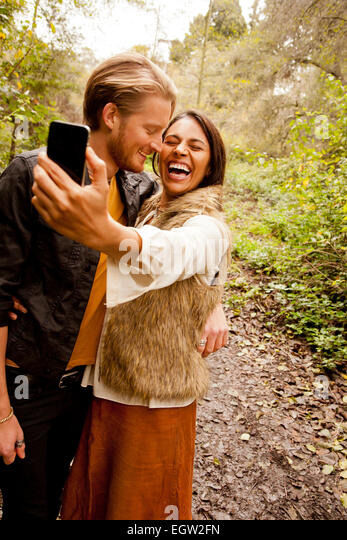 Woman and man taking a selfie in the woods. - Stock-Bilder