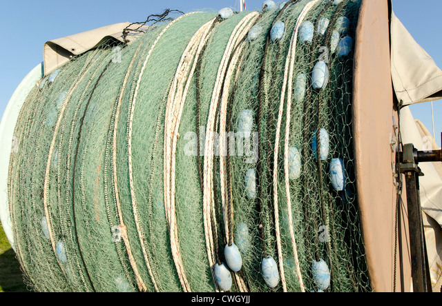 Monofilament trawler fishing net and floats rolled up for storage out of water, Wanchese North Carolina Outer Banks - Stock Image