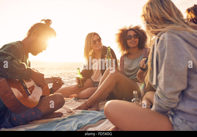 Group of young people sitting at the beach together while young man playing guitar. Group of friends partying on - Stock Image