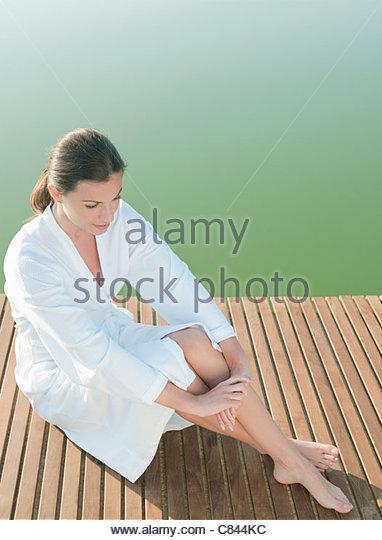 Woman sitting on dock of lake - Stock Image