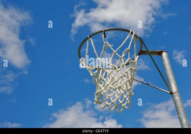 Abstract perspective of a netball rim with net against a blue sky and cloud background. - Stock Image