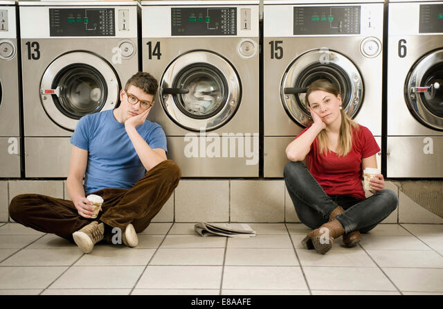 Portrait of young couple sitting on floor - Stock Image