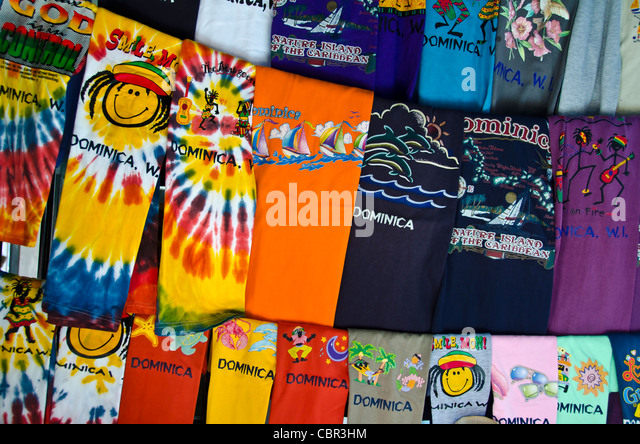 Rows of brightly colored Dominica t-shirts near the Roseau cruise port - Stock Image