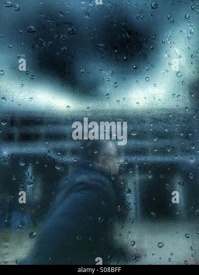 Man running in the rain - Stock Image