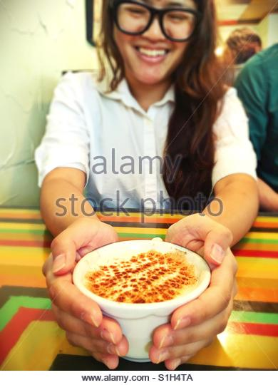A young woman holding a cup of chai. - Stock Image
