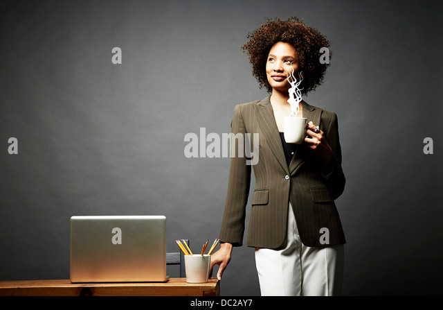 Woman holding cup of steaming hot beverage - Stock Image