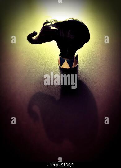 A circus elephant figurine and shadow. - Stock Image