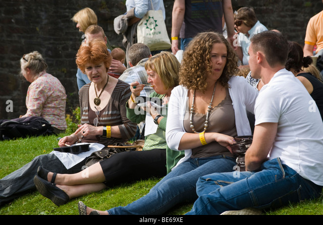 People eating snacks sat on grass bank in castle grounds during Abergavenny Food Festival Monmouthshire South Wales - Stock Image