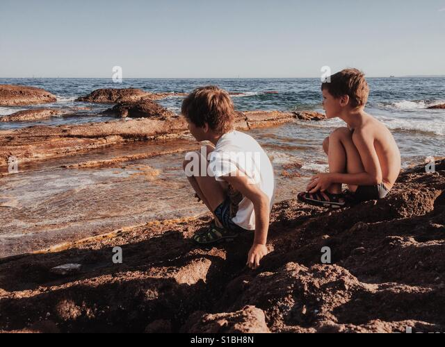 Two boys on the beach - Stock Image