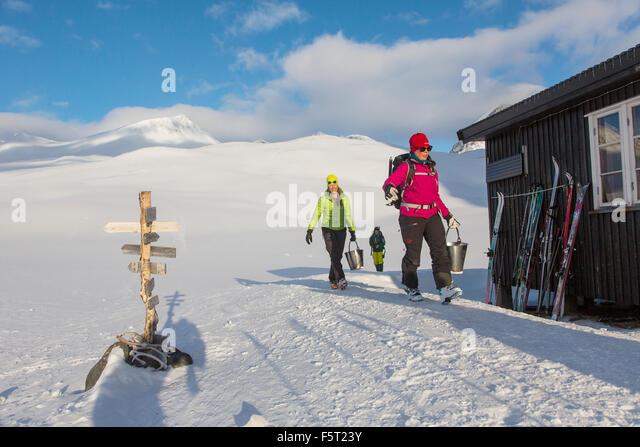 Sweden, Lapland, Women carrying water buckets - Stock Image