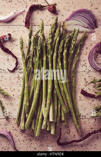 high-angle shot of a bunch of wild asparagus on a rustic wooden surface - Stock Image
