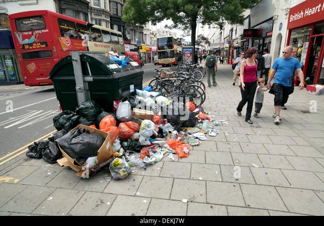 Rubbish piled around an overflowing skip of litter, Brighton. - Stock Image