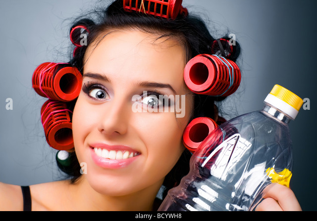 Young housewife with hair rollers and bottle - Stock Image