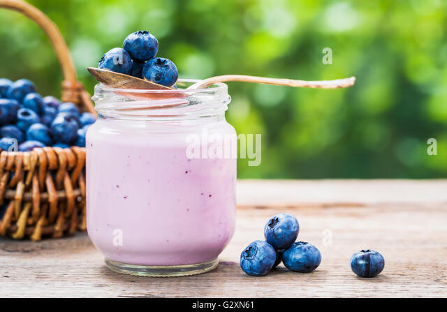 Blueberries yogurt in jar, basket of berries and saucer with bilberries on table outdoors. - Stock Image