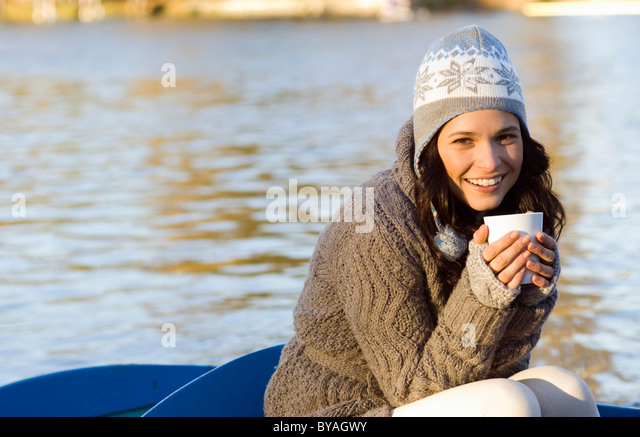 Woman holding mug in row boat - Stock Image