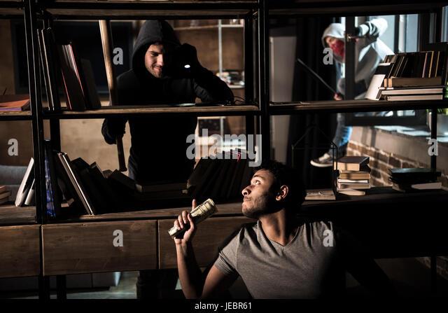 Scared man hiding from burglars behind bookshelves, house robbery scene - Stock Image