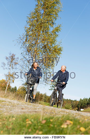 Sweden, Sodermanland, Man and woman cycling - Stock Image