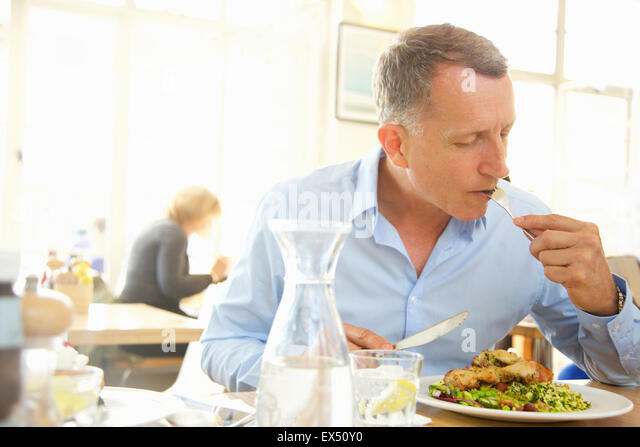Mature Man Eating Lunch at Restaurant - Stock Image