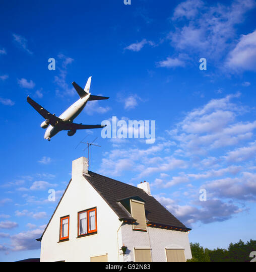 large jet aircraft on landing approach over suburban housing - Stock Image