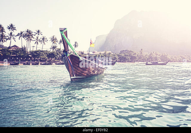 Retro filtered picture of boat and tropical island. - Stock-Bilder