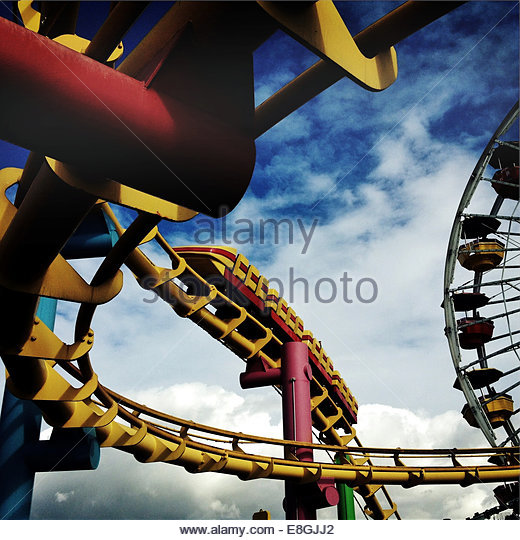 Low angle view of roller coaster and big wheel, Santa Monica, California, America, USA - Stock Image