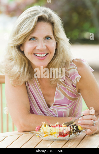 Portrait of a mature woman eating an ice cream - Stock-Bilder