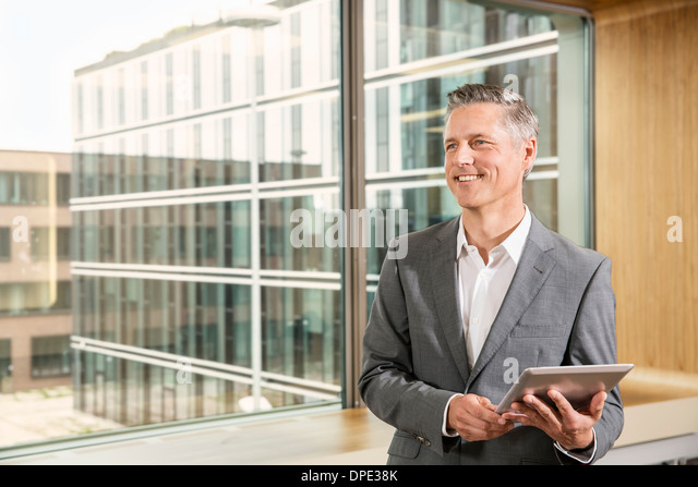 Businessman using digital tablet - Stock-Bilder