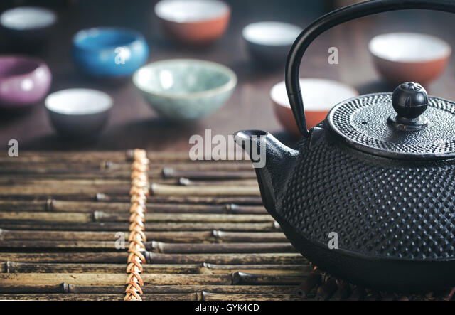 Traditional oriental teapot on bamboo placemat - Stock Image