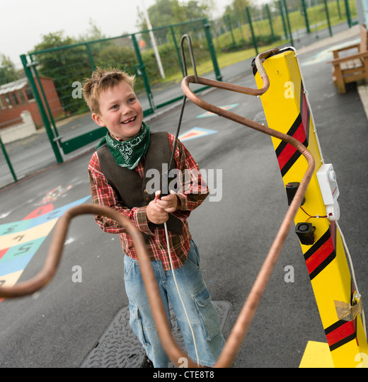 A boy testing his skill and eye-hand co-ordination on buzz wire maze game of manual dexterity avoiding ringing the - Stock Image