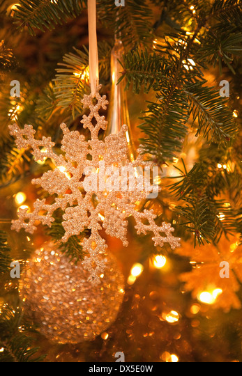 Sparkly snowflake and ball ornaments hanging in illuminated Christmas tree - Stock Image