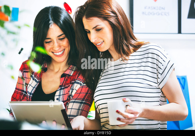 Two female fashion bloggers using digital tabletin the office - Stock Image