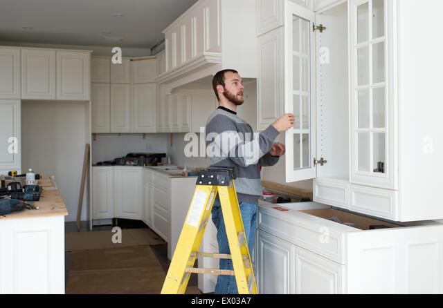 Carpenter installing kitchen cabinet - Stock-Bilder