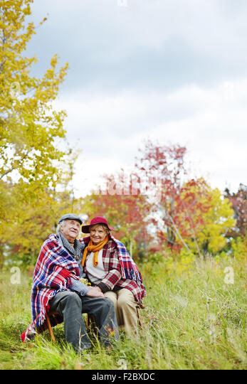 Old man and woman in warm clothes enjoying rest in park - Stock Image