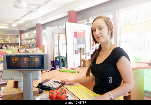 Woman working in organic food market, serving at cash register - Stock Image