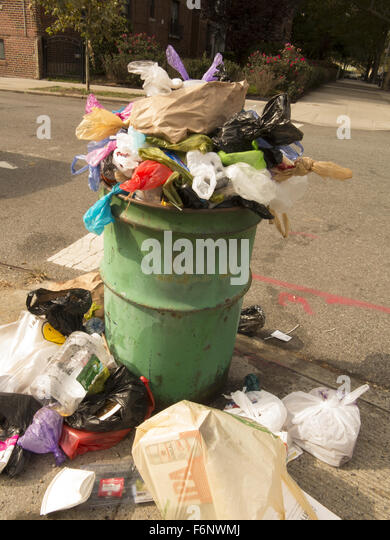 Overflowing garbage can in Brooklyn, NY. - Stock Image