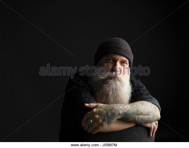 Portrait confident tattooed hipster man with long gray beard against black background - Stock Image