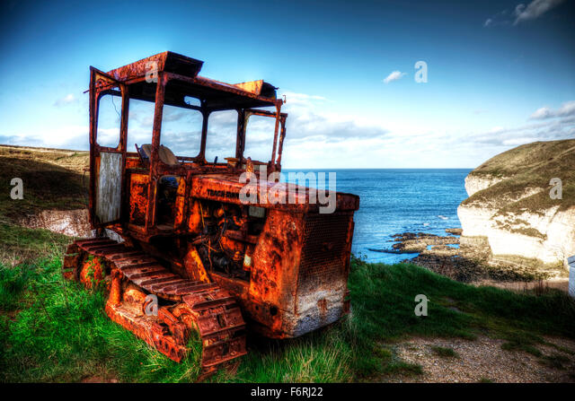 Rusty rusted caterpillar trach marshall tractor north landing at flamborough head yorkshire old overlook beach bay - Stock Image