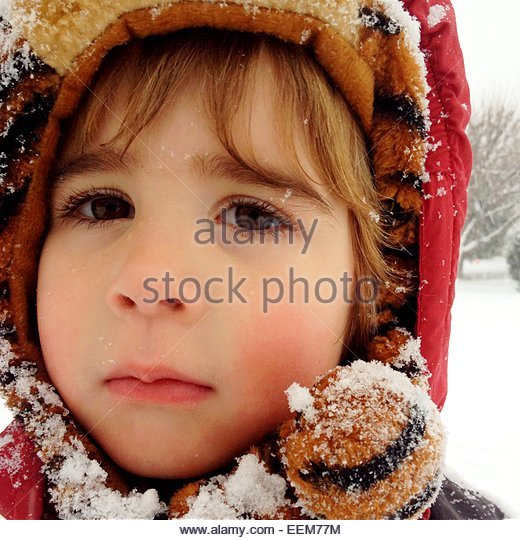 Headshot of a boy wearing hooded winter clothing sprinkled with snow - Stock Image