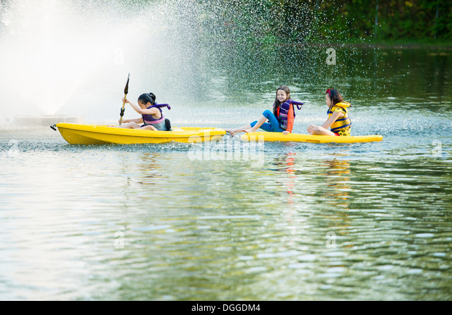 Girls canoeing on lake - Stock Image