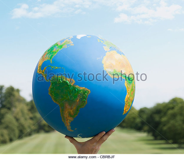 Hand holding large globe outdoors - Stock Image