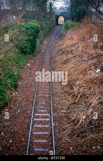 photograph of rubbish strewn railway track and bridge - Stock Image