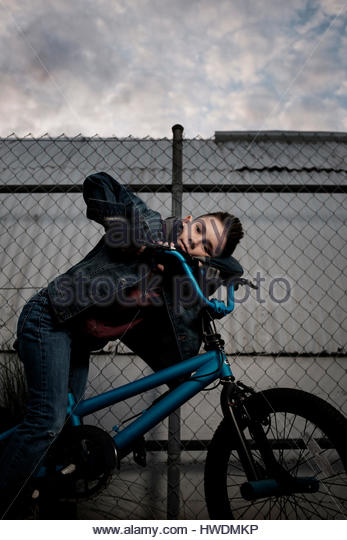 Boy on his bicycle, fence in background - Stock-Bilder