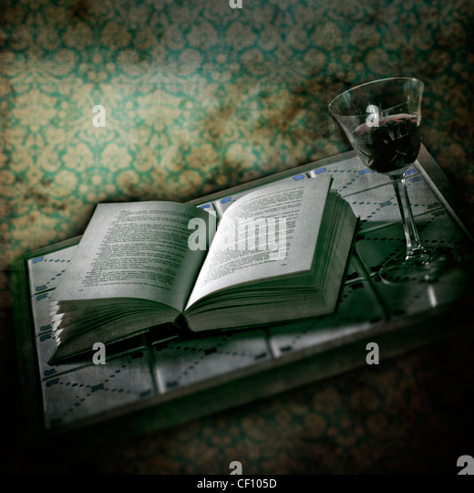 an open book on a table with old tiles and a glass of red wine in a room with an old wallpaper - Stock Image