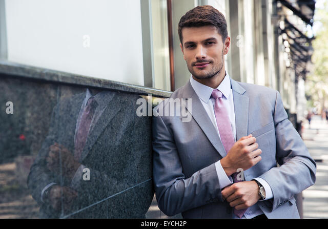 Confident businessman standing outdoors and looking at camera - Stock Image