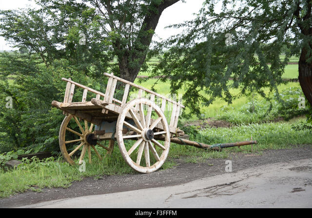 Bullock cart without bulls parked at the side of the road ; India - Stock Image