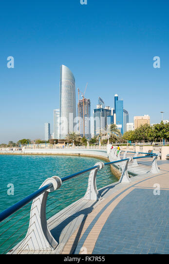 View along waterfront of Corniche towards modern office towers in Abu Dhabi United Arab Emirates - Stock Image