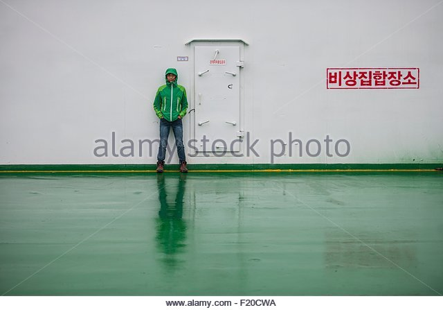 Woman standing next to door on ferry to Jeju Island, South Korea - Stock Image